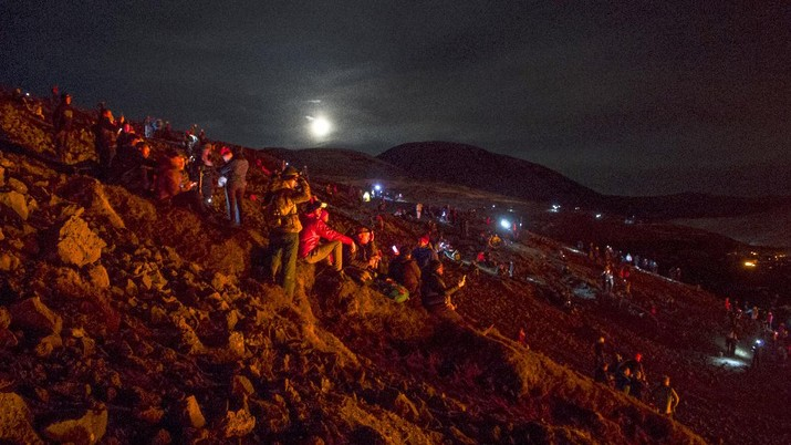 People watch as lava flows from an eruption of a volcano on the Reykjanes Peninsula in southwestern Iceland late on Monday, March 29, 2021. Iceland's latest volcano eruption is still attracting crowds of people hoping to get close to the gentle lava flows. (AP Photo/Marco Di Marco)