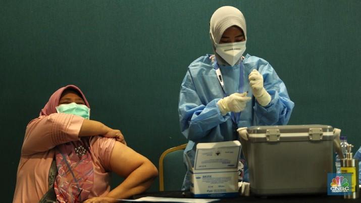 Petugas menyuntikkan vaksin Covid-19 kepada penerima vaksin di Senayan City, Jakarta, Rabu (7/4/2021). Senayan City memfasilitasi vaksinasi dosis pertama bagi lansia dan tenaga pengajar yang ditargetkan untuk 500 orang per hari dari tanggal 7-10 April 2021.  (CNBC Indonesia/ Tri Susilo)