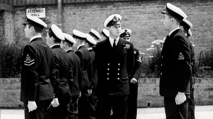 FILE - In this July 31, 1947 file photo, Lieut. Philip Mountbatten, as he was then called, center, inspects his men at the Petty Officers' Training Center at Corsham, England. There certainly won't be fuss. Count on that. When Britain's Prince Philip reaches the grand age of 99 on Wednesday, he will spend it quietly and in much the same way he's spent most of his adult life: beside Queen Elizabeth II. Prince Philip was born into the Greek royal family but spent almost all of his life as a pillar of the British one. His path was forged when he married the heir to the British throne, and a promising naval career was cut short when his wife suddenly became Queen Elizabeth II. Nevertheless, he set about forging a place for himself as royal consort. He was a patron of charities and a supporter of projects for young people. He was married for more than 73 years and was still carrying out royal engagements into his late 90s. (AP Photo/File)