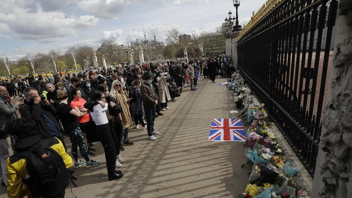 People view flowers left in front of the gate at Buckingham Palace in London, after the announcement of the death of Britain's Prince Philip, Friday, April 9, 2021. Buckingham Palace officials say Prince Philip, the husband of Queen Elizabeth II, has died. He was 99. Philip spent a month in hospital earlier this year before being released on March 16 to return to Windsor Castle. (AP Photo/Matt Dunham)
