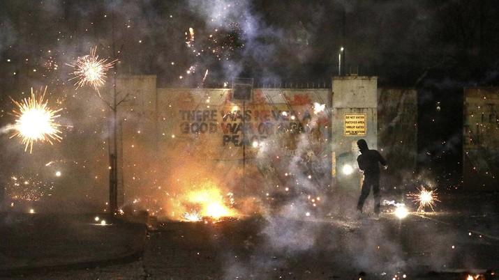 Kelompok nasionalis Irlandia dan loyalis pro-Inggris saling melempar kembang api, batu, dan bom molotov pada Rabu (7/4) malam. (AP/Peter Morrison)
