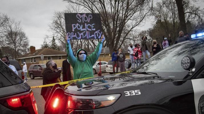 Warga merusak mobil polisi setelah penembakan fatal seorang warga kulit hitam di Minneapolis, AS. (AP/Christian Monterrosa)