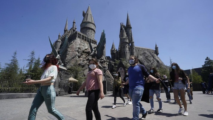 Young people wear mandatory face masks at the Wizarding World of Harry Potter at Universal Studios Hollywood theme park as it officially reopens to the public at 25% capacity with COVID-19 protocols in place in Los Angeles, Friday, April 16, 2021. (AP Photo/Damian Dovarganes)