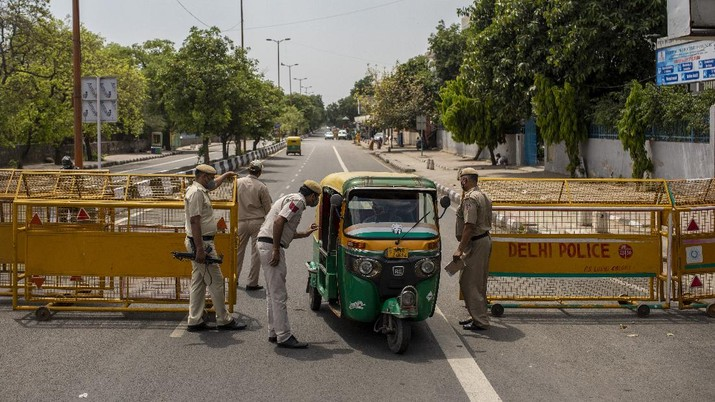 Delhi Police officers stop an autorickshaw at a check point during a weekend lockdown in New Delhi, India, Saturday, April 17, 2021. Over 200,000 new infections were detected in the past 24 hours, and major cities, like Mumbai and New Delhi, are under virus restrictions. (AP Photo/Altaf Qadri)