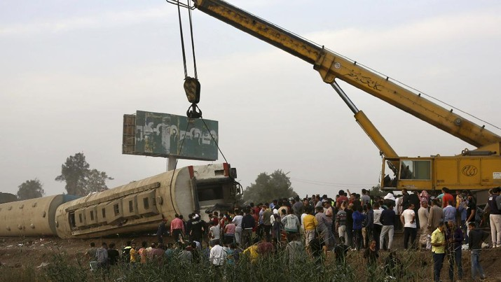 A crane is used to lift a part of a passenger train that derailed injuring some 100 people, near Banha, Qalyubia province, Egypt, Sunday, April 18, 2021. At least eight train wagons ran off the railway, the provincial governor's office said in a statement. (AP Photo/Fadel Dawood)