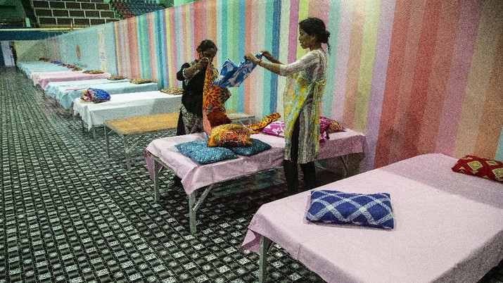 Workers arrange beds at a COVID-19 treatment facility newly set up at an indoor stadium in Gauhati, India, Monday, April 19, 2021. India now has reported more than 15 million coronavirus infections, a total second only to the United States. (AP Photo/Anupam Nath)