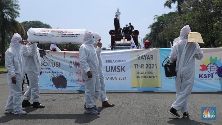Sejumlah masa aksi buruh memakai hazmat dan membawa keranda mayat menggelar taterikal di Patung Kuda Arjuna Wiwaha, Jakarta, Rabu (21/4/2021). (CNBC Indonesia/Tri Susilo)
