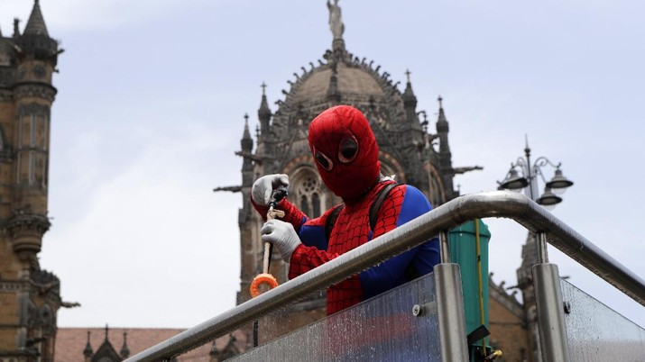 Indian social worker Ashok Kurmi dressed as spider man sanitizes the area around Chhatrapati Shivaji Maharaj train Terminus during a lockdown imposed to curb the spread of COVID-19 in Mumbai, India, Wednesday, April 21, 2021. (AP Photo/Rajanish Kakade)