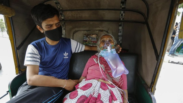 A COVID-19 patient wearing oxygen mask waits inside an auto ricksha to be attended and admitted to a dedicated COVID-19 government hospital in Ahmedabad, India, Saturday, April 17, 2021. The global death toll from the coronavirus topped a staggering 3 million people Saturday amid repeated setbacks in the worldwide vaccination campaign and a deepening crisis in places such as Brazil, India and France. (AP Photo/Ajit Solanki)