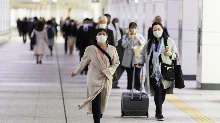 People wearing face masks to help curb the spread of the coronavirus walk towards a train station in Tokyo on Friday, April 23, 2021. (AP Photo/Hiro Komae)