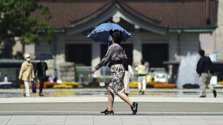 A woman wearing a protective mask to help curb the spread of the coronavirus walks at a park Wednesday, April 21, 2021, in Tokyo. The Japanese capital confirmed more than 840 new coronavirus cases on Wednesday. (AP Photo/Eugene Hoshiko)