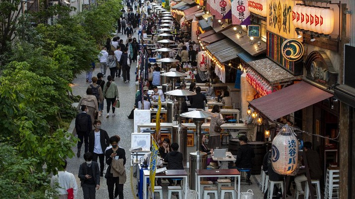 People sit in the outdoor seating areas of restaurants and bars Tuesday, April 20, 2021, in Tokyo. (AP Photo/Kiichiro Sato)