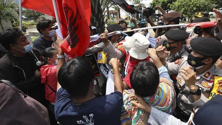 Aktivis bentrok dengan petugas polisi saat mereka dibubarkan selama unjuk rasa menentang kudeta militer Myanmar di dekat Sekretariat Perhimpunan Bangsa-Bangsa Asia Tenggara (ASEAN) menjelang pertemuan para pemimpin di Jakarta, Indonesia, Sabtu, 24 April 2021. (AP/Dita Alangkara)