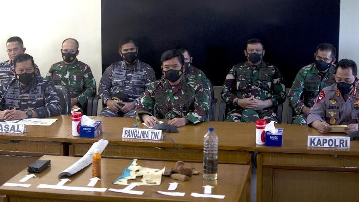 Panglima TNI Angkatan Laut Yudo Margono, kiri depan, Panglima TNI Hadi Tjahjanto, tengah, dan Kapolri Listyo Sigit Prabowo, kanan, berbicara kepada media saat mereka menampilkan puing-puing yang ditemukan di perairan selama pencarian kapal selam TNI AL KRI Nanggala di Ngurah Pangkalan Udara Militer Rai di Bali, Sabtu (24/4/2021). (AP/Firdia Lisnawati)