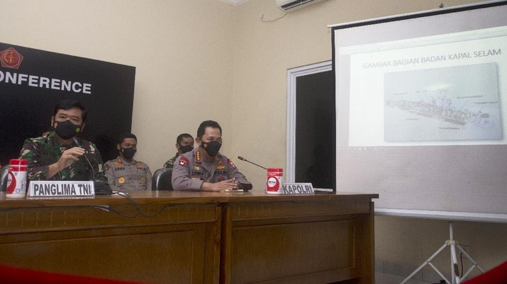 Indonesian Military chief Hadi Tjahjanto, left, shows an image of the Indonesian Navy submarine KRI Nanggala on a screen during a news conference at Ngurah Rai Military Air Base in Bali, Indonesia on Sunday, April 25, 2021. Indonesia's military on Sunday officially admitted there was no hope of finding survivors from a submarine that sank and broke apart last week with 53 crew members aboard, and that search teams had located the vessel's wreckage on the ocean floor. (AP Photo/Firdia Lisnawati)