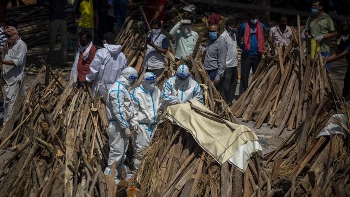 People perform rituals next to a funeral pyre for a family member who died of COVID-19 at a ground that has been converted into a crematorium for mass cremation of COVID-19 victims in New Delhi, India, Saturday, April 24, 2021. Delhi has been cremating so many bodies of coronavirus victims that authorities are getting requests to start cutting down trees in city parks, as a second record surge has brought India's tattered healthcare system to its knees. (AP Photo/Altaf Qadri)