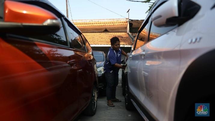 Pekerja membersihkan mobil rental yang terparkir di kawasan Tanjung Priok, Jakarta, Selasa, (27/4). Salah satu pemilik jasa rental mobil rentcartopiq Taufiq mengatakan, musim mudik di bulan ramadhan ini masih sepi order.