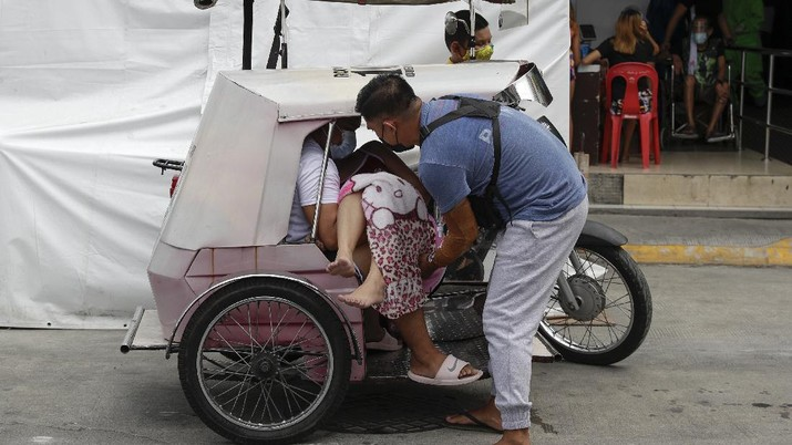 A man carries a sick woman from a pedicab as they bring her to the emergency area of the hospital that is crowded with suspected COVID-19 patients in Manila, Philippines on Monday, April 26, 2021. COVID-19 infections in the Philippines surged past 1 million Monday in the latest grim milestone as officials assessed whether to extend a monthlong lockdown in Manila and outlying provinces amid a deadly spike or relax it to fight recession, joblessness and hunger. (AP Photo/Aaron Favila)