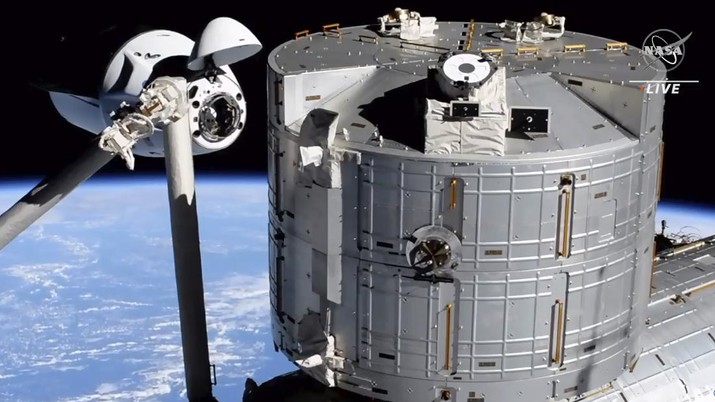 In this image made from NASA TV, the SpaceX Crew Dragon spacecraft, left, approaches to the international space station, Saturday, April 24, 2021. The recycled SpaceX capsule carrying four astronauts arrived at the International Space Station on Saturday, the third high-flying taxi ride in less than a year for Elon Musk's company.(NASA via AP)