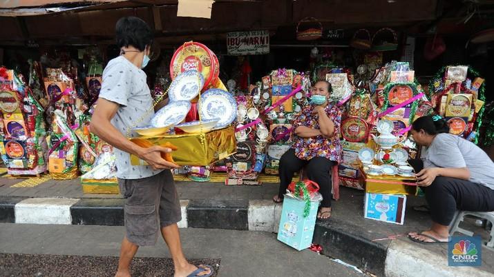 Pedagang menyelesaikan pembungkusan parcel di kawasan Barito Jakarta, Rabu (28/4/2021). Pedagang parcel musiman tersebut menjual parcelnya mulai dari harga 250 ribu hingga 3 juta tergantung dari model parcel yang diminta pembeli. Isi parcel pun beragam, mulai dari makanan ringan, minuman hingga piring dan gelas. Namun para pedagang mulai ramai pesanan H-14 untuk perkantoran dan perorangan. Hal serupa juga terjadi di Jl. Barito penjual parcel dikawasan ini mulai kebanjiran order, salah satunya Yuni pedagang asal Jawa tengah mengaku dirinya ramai pesanan untuk perkantoran hingga perorangan.