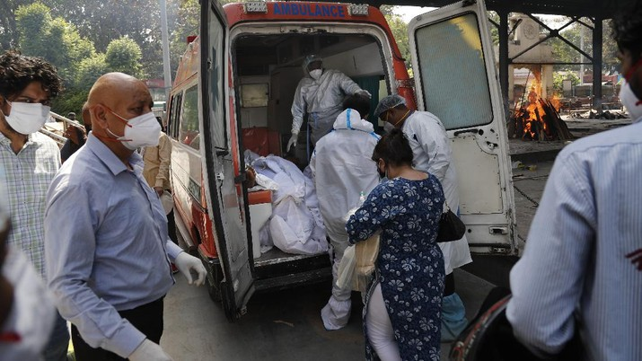 FILE - In this April 19, 2021, file photo, health workers prepare to take out from an ambulance bodies of six people who died of COVID-19 for cremation, in New Delhi, India. India crossed a grim milestone Wednesday, April 28, 2021 of 200,000 people lost to the coronavirus as a devastating surge of new infections tears through dense cities and rural areas alike and overwhelms health care systems on the brink of collapse. (AP Photo/Manish Swarup)