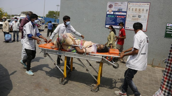 Health workers bring a patient to be admitted at a government COVID-19 hospital in Ahmedabad, India, Tuesday, April 27, 2021. Coronavirus cases in India are surging faster than anywhere else in the world. (AP Photo/Ajit Solanki)