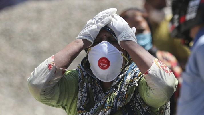 A relative of a person who died of COVID-19 reacts at a crematorium in Jammu, India, Sunday, April.25, 2021. (AP Photo/Channi Anand)