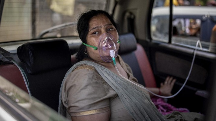 FILE - In this April 24, 2021, file photo, a COVID-19 patient sits inside a car and breathes with the help of oxygen provided by a Gurdwara, a Sikh house of worship, in New Delhi, India. India crossed a grim milestone Wednesday, April 28, 2021 of 200,000 people lost to the coronavirus as a devastating surge of new infections tears through dense cities and rural areas alike and overwhelms health care systems on the brink of collapse. (AP Photo/Altaf Qadri)