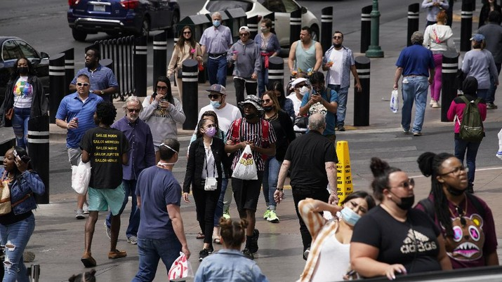 Masked and unmasked pedestrians walk along the Las Vegas Strip, Tuesday, April 27, 2021, in Las Vegas. The Centers for Disease Control and Prevention eased its guidelines Tuesday on the wearing of masks outdoors, saying fully vaccinated Americans don't need to cover their faces anymore unless they are in a big crowd of strangers.(AP Photo/John Locher)