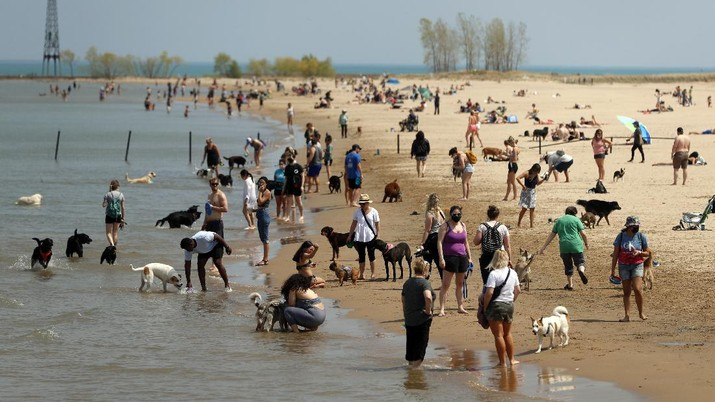 People gather with their dogs in Chicago's Montrose Dog Beach, Tuesday, April 27, 2021. The Centers for Disease Control and Prevention eased its guidelines Tuesday on the wearing of masks outdoors, saying fully vaccinated Americans don't need to cover their faces anymore unless they are in a big crowd of strangers. (AP Photo/Shafkat Anowar)