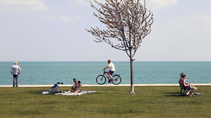 People spend time as they take advantage of warm spring weather along Lake Michigan on Tuesday, April 27, 2021, at Montrose Beach in Chicago. The Centers for Disease Control and Prevention eased its guidelines Tuesday on the wearing of masks outdoors, saying fully vaccinated Americans don't need to cover their faces anymore unless they are in a big crowd of strangers. (AP Photo/Shafkat Anowar)