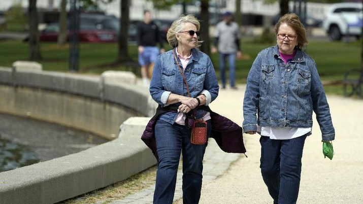 Donna Anderson, left, walks with her friend Christine White, Tuesday, April 27, 2021, in Olympia, Wash. Both women said they are fully vaccinated and have felt comfortable recently in not wearing masks when they are outdoors. On Tuesday, the Centers for Disease Control and Prevention eased its guidelines on the wearing of masks outdoors, saying fully vaccinated Americans don't need to cover their faces anymore unless they are in a big crowd of strangers. (AP Photo/Ted S. Warren)