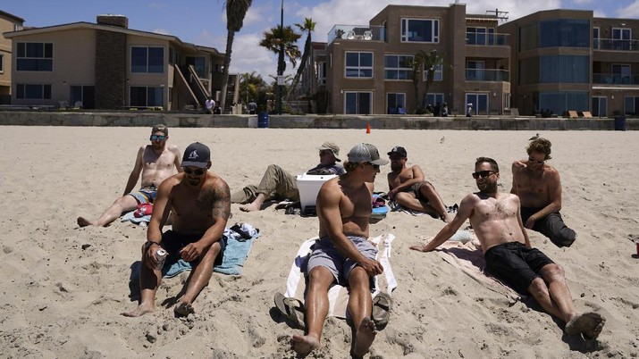A group of men in town for a bachelor's party sit on the beach Tuesday, April 27, 2021, in San Diego. Many in the group had already been vaccinated. U.S. health officials say fully vaccinated Americans don't need to wear masks outdoors anymore unless they are in a big crowd of strangers. And unvaccinated people can drop face coverings in some cases, too. (AP Photo/Gregory Bull)