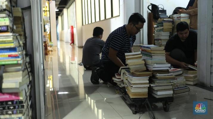 Sejumlah pedagang merapikan buku bacaan di Pasar Kenari, Jakarta, Kamis (29/4/2021). Pasar Buku Kenari sangat sepi dari pengunjung di tengah masa pandemi Covid-19. Pantauan CNBC Indonesia sesekali ada warga yang melihat - lihat bahkan membeli buku satu atau dua di Pasar ini. Pasar Buku Kenari menjual berbagai macam buku mulai buku bacaan hingga komik, buku yang dijual merupakan buku bekas ataupun buku baru. Novelia (19) mewakili pedagang buku yang terdampak pandemi covid mengatakan