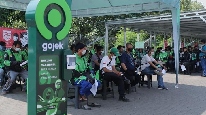 Petugas kesehatan menyuntikkan vaksin dosis pertama kepada driver Gojek di Kemayoran, Jakarta, Kamis (29/4/2021). Halodoc dan Gojek berkolaborasi hadirkan pos pelayanan Covid-19 melalui metode Drive thru dan melayani 1.500 dosis vaksin setiap harinya untuk memperkuat upaya Kementerian Kesehatan RI dalam mempercepat Vaksinasi Covid-19 di Indonesia.  (CNBC Indonesia/ Tri Susilo)