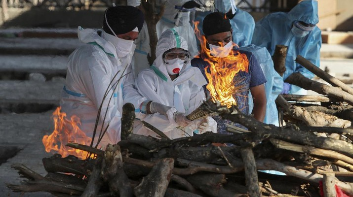 Family members of a person who died due to COVID-19 light the funeral pyre at a crematorium in Jammu, India, Monday, April 26, 2021. (AP Photo/Channi Anand)