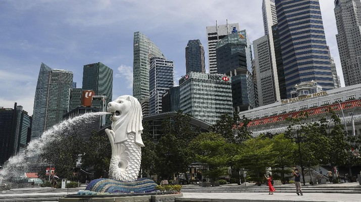 People are dwarfed against the financial skyline as they take photos of the Merlion statue along the Marina Bay area in Singapore, Tuesday, June 30, 2020. (AP Photo/Yong Teck Lim)