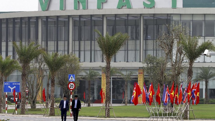 Two men walk outside the main entrance of VinFast, an automotive startup manufacturer in Hai Phong, Vietnam Wednesday, Feb. 27, 2019. As North Korean leader Kim Jong Un prepared for his second summit with President Donald Trump, top members of his delegation made a whirlwind tour of one of Vietnam's most successful conglomerates. (AP Photo/Minh Hoang)