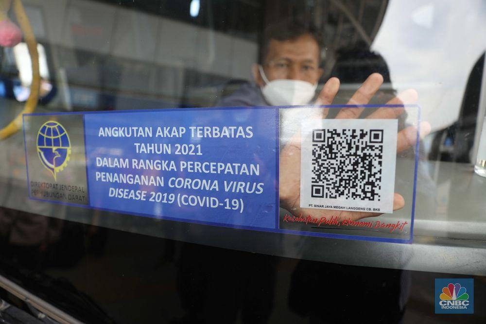 Penempelan stiker di Terminal bus  Pulogebang. (CNBC Indonesia/Muhammaad Sabki)