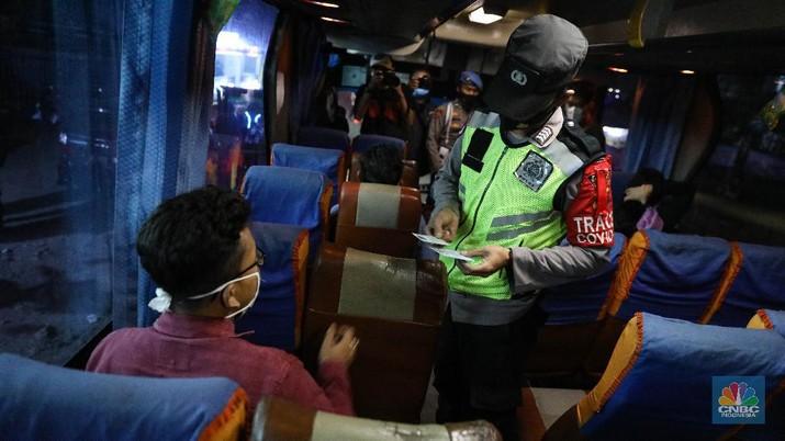 Petugas kepolisian memeriksa dokumen pengendara yang melintas di Pospam Gerem, Cilegon, Banten, Kamis (6/5/2021) dini hari. Pemeriksaan tersebut terkait larangan mudik lebaran 2021 yang dimulai dari tanggal 6 hingga 17 Mei sebagai upaya mengantisipasi risiko peningkatan kasus penularan COVID-19 jelang perayaan Hari Raya Idul Fitri 1442 H. (CNBC Indonesia/Andrean Kristianto)