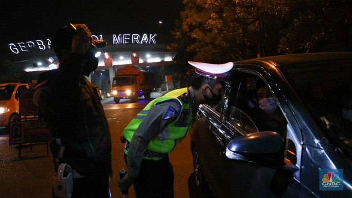 Petugas kepolisian memeriksa dokumen pengendara yang melintas dari arah Jakarta menuju Merak di pintu Gerbang Tol Merak, Banten, Kamis (6/5/2021) dini hari. Pemeriksaan tersebut terkait larangan mudik lebaran 2021 yang dimulai dari tanggal 6 hingga 17 Mei sebagai upaya mengantisipasi risiko peningkatan kasus penularan COVID-19 jelang perayaan Hari Raya Idul Fitri 1442 H. (CNBC Indonesia/Andrean Kristianto)