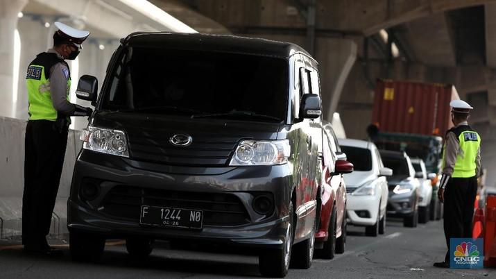 Sejumlah petugas Kepolisian memeriksa dokumen pengendara yang melintas di pos penyekatan pemudik Tol Cikarang Barat, Kabupaten Bekasi, Jawa Barat, Selasa (11/5/2021). Petugas gabungan memperketat pemeriksaan dokumen kendaraan yang melintasi pos penyekatan pemudik jelang H-2 perayaan Hari Raya Idul Fitri 1442 H guna memutus rantai penyebaran wabah COVID-19.  (CNBC Indonesia/Andrean Kristianto)