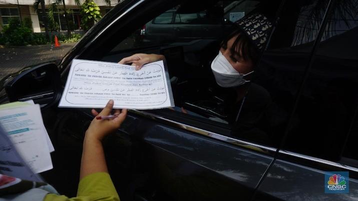 Warga menunaikan zakat fitrah dalam acara ulan suci Ramadan 1442 Hijriah di Gerai Zakat Infaq dan Shodaqoh drive thru di Masjid Nurul Hidayah, Jakarta, Selasa (11/5/2021). (CNBC Indonesia/Tri Susilo)