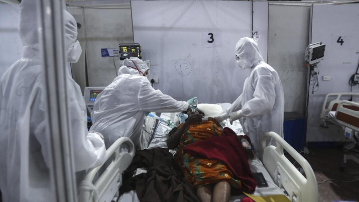 Health workers give water to a patient at the BKC jumbo field hospital, one of the largest COVID-19 facilities in Mumbai, India, Thursday, May 6, 2021. (AP Photo/Rafiq Maqbool)
