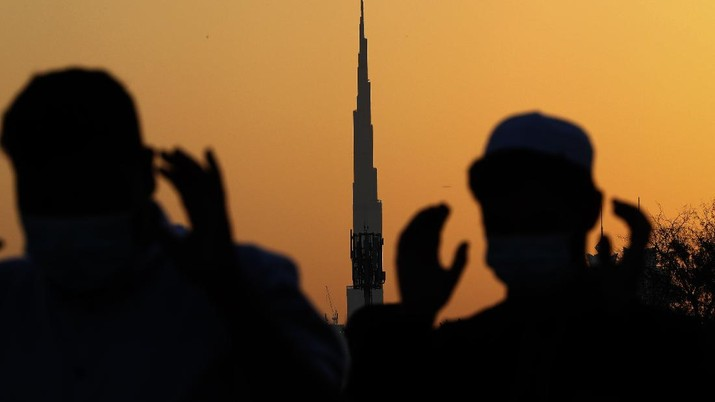 With the world's tallest building, Burj Khalifa, in background, Muslim men wearing masks to curb the spread of coronavirus outbreak perform an Eid al-Fitr prayer marking the end of the holy fasting month of Ramadan in Dubai, United Arab Emirates, Thursday, May 13, 2021. (AP Photo/Kamran Jebreili)