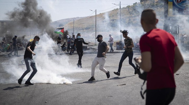 Palestinian protestors throw back a teargas canister during clashes with Israeli troops at the Hawara checkpoint, south of the West Bank city of Nablus, Friday, May 14, 2021. Health officials say several Palestinians were killed by Israeli army fire, at protests that took place in several locations across the West Bank of Friday. (AP Photo/Majdi Mohammed)