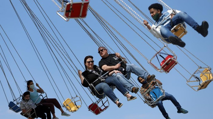 People enjoy their time in a wave swinger Friday, May 14, 2021 at Chicago's Navy Pier. The U.S. Centers for Disease Control and Prevention eased its guidelines, saying fully vaccinated people can resume activities without wearing masks. (AP Photo/Shafkat Anowar)