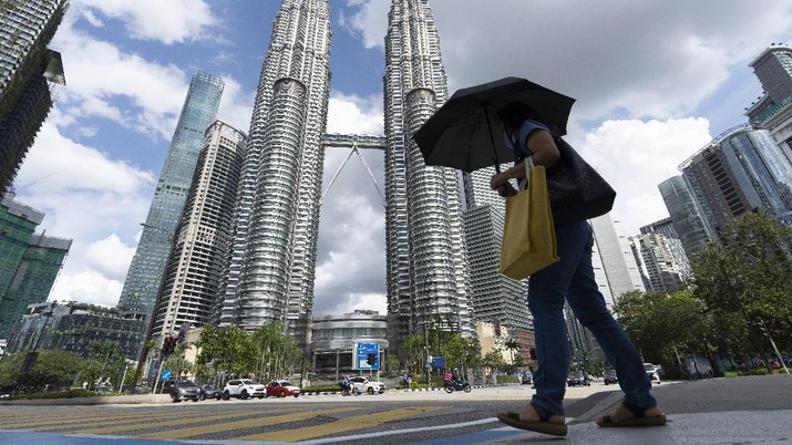 A woman wearing a face mask walks in front of the Twin Towers during the first day of third Movement Control Order (MCO) in Kuala Lumpur, Malaysia, Friday, May 7, 2021. Kuala Lumpur and few other cities will be placed under the Movement Control Order (MCO) as the number of COVID-19 cases and clusters continue to rise. (AP Photo/Vincent Thian)