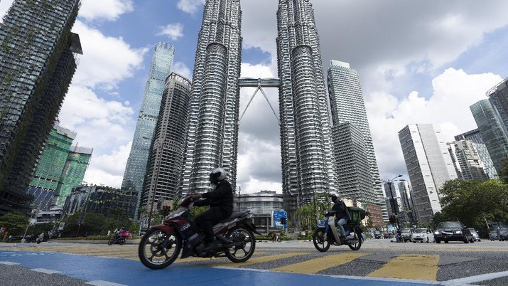 Motorists ride past wearing face masks in front of the Twin Towers during the first day of third Movement Control Order (MCO) in Kuala Lumpur, Malaysia, Friday, May 7, 2021. Kuala Lumpur and few other city will be placed under the Movement Control Order (MCO) as the number of COVID-19 cases and clusters continue to increase. (AP Photo/Vincent Thian)
