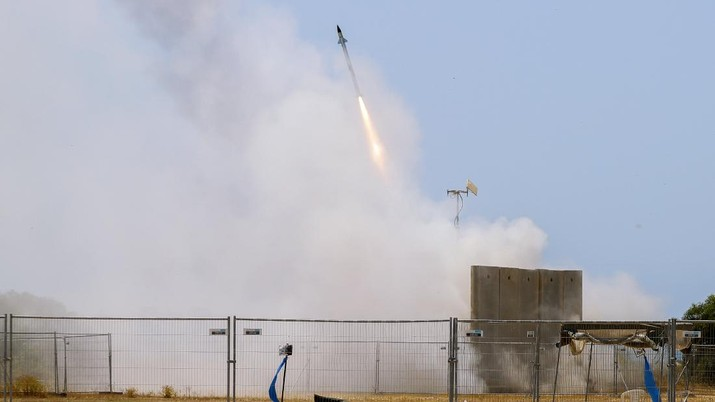 A Israeli soldier takes cover as an Iron Dome air defense system launches to intercept a rocket from the Gaza Strip, in Ashkelon, southern Israel, Tuesday, May 11, 2021. (AP Photo/Ariel Schalit)